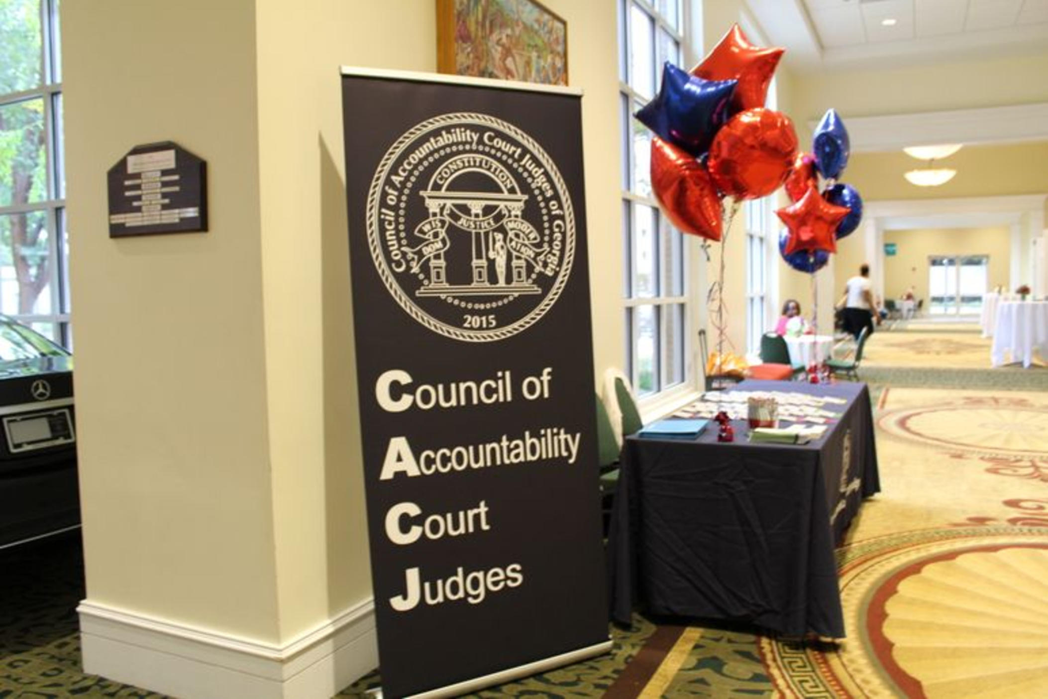 Table at the conference with balloons and a CACJ banner.