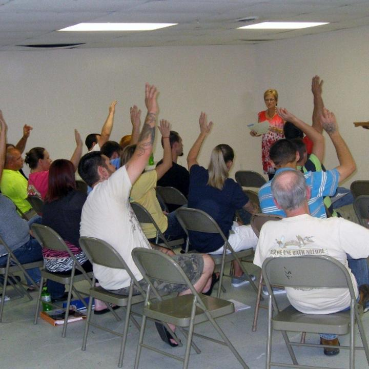 A group of people from court teams being led by an instructor, many with hands raised.